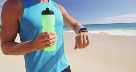 hydratace : Close-up view of unrecognizable sportsman in blue sleeveless sport shirt, standing on beach, holding a bottle of water and looking at sport watch on hand. Seascape on background. Copy space