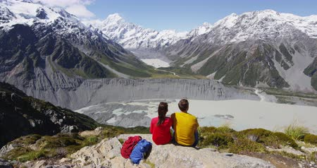 épico : Couple sitting at mount top during hike. Back view of two hikers having rest at the top of mountain, sitting close to each other and enjoying picturesque view of high snowy tops and lakes Stock Footage