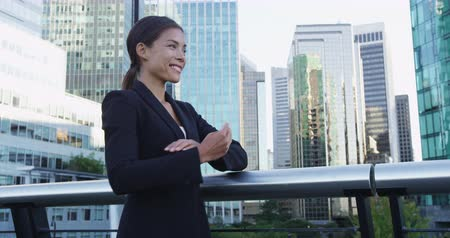 self motivated : Low angle of cheerful young Asian businesswoman in black jacket standing over skyscraper background with arms crossed and closed eyes and smiling happily. Copy space Stock Footage