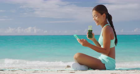 preslenmiş : Woman drinking vegetable Green detox smoothie using smart phone after fitness running workout on summer day. Fitness and healthy lifestyle concept with beautiful fit mixed race Asian Caucasian model. Stok Video
