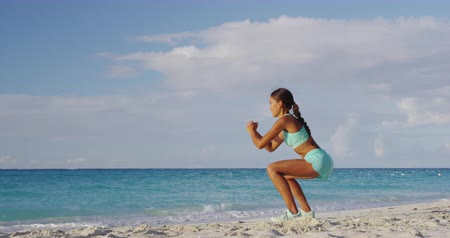 bodyweight : Squat pulses - Fitness young woman working out glutes with bodyweight workout doing squat pulse exercises on beach. Asian sporty girl squatting legs as part of an active and fit life. Stock Footage