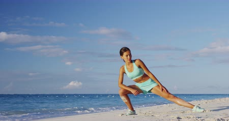 stehno : Runner woman stretching legs with lunge hamstring stretch exercise leg stretches. Fitness female athlete relaxing on beach doing a warm-up before her strength training cardio workout.