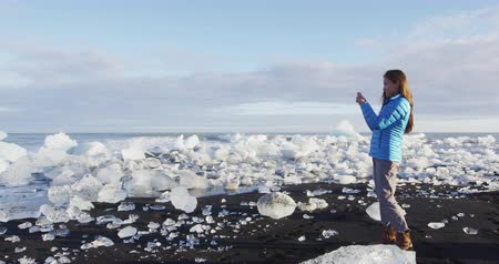 photograph : Iceland nature at Jokulsarlon Iceberg beach. Woman tourist taking photograph with mobile phone by Jokulsarlon glacial lagoon. Breidamerkursandur Ice beach.