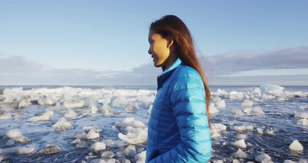 iceberg : Woman walking on Diamond beach with ice from jokulsarlon glacial lagoon on Iceland.