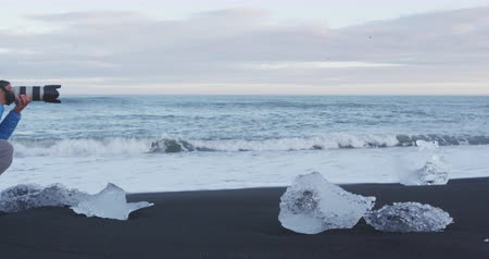 алмаз : Photographer taking photos in nature on Iceland Diamond Beach with Ice. Iceland. Стоковые видеозаписи