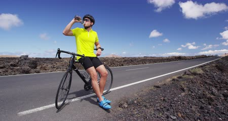 バイクに乗る人 : Athlete cyclist man drinking water after intensive cycling biking training, Healthy active lifestyle sports fitness man resting on bike after exercise 動画素材