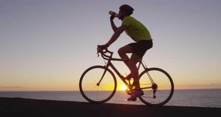 cyclists : Athlete cyclist man drinking water after intensive cycling biking training, Healthy active lifestyle sports fitness man exercising at sunset. SLOW MOTION RED EPIC.