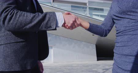 casual wear businessman : Handshake - business people shaking hands. Handshake between business man and business woman outdoors by business building. Casual wear, young people in their 30s. shaking hands close up. SLOW MOTION Stock Footage