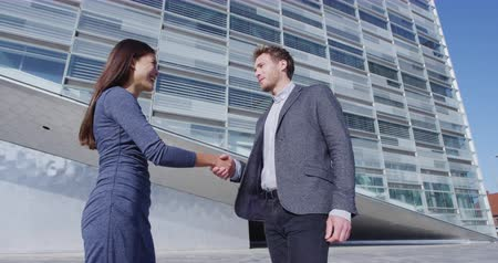 kezek : Business Handshake - business people shaking hands. Handshake between business man and woman outdoors by business building. Casual wear, young people in their 30s. shaking hands close up. SLOW MOTION