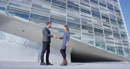 üzleti öltöny : Business Handshake - business people meeting shaking hands. Handshake between business man and woman outdoors by office building. Casual clothing, young people, 30s. shaking hands closeup. SLOW MOTION Stock mozgókép