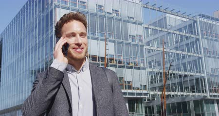 solicitor : Phone - businessman talking on mobile smartphone in city business district. Confident happy young businessman talking on smartphone outdoors. Young urban male professional. RED EPIC SLOW MOTION.