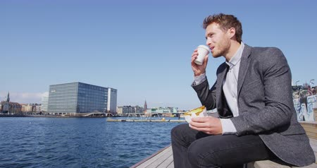 kodaň : Lunch break - business man eating lunch drinking coffee outside in city. Young urban professional businessman sitting down enjoying coffee break outdoors in downtown Copenhagen, Denmark, SLOW MOTION.