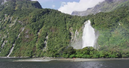 Új zéland : Milford Sound Waterfall in Fiordland National Park, New Zealand South Island, Southern Alps. Lady Elizabeth Bowen Falls nature landscape scenery seen from cruise ship. Tourist destination, New Zealand Stock mozgókép