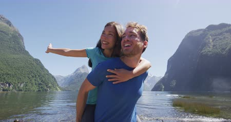 ırklararası : Couple in love having fun outdoors in nature piggybacking laughing and smiling enjoying active outdoor lifestyle hiking in Milford Sound New Zealand by Mitre Peak in Fiordland.