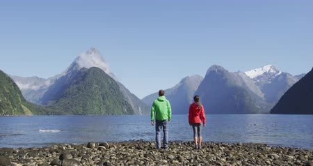 nový zéland : New Zealand - tourists hiking standing looking at Milford Sound enjoying iconic view and famous tourist destination and landmarks in Fiordland National Park, South Island, Southern Alps, New Zealand.