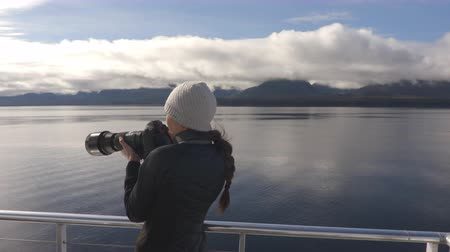 аляскинским : Alaska tourist wildlife photographer enjoying travel vacation cruise in Misty Fiords National Monument (aka Misty Fjords) taking pictures photographing the travel adventure in Alaska. Стоковые видеозаписи