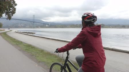 Ванкувер : Woman Cyclist biking in Stanley Park by Lions Gate Bridge on Vancouver Seawall. Bike rental is a popular tourist activity in Vancouver, British Columbia, Canada.