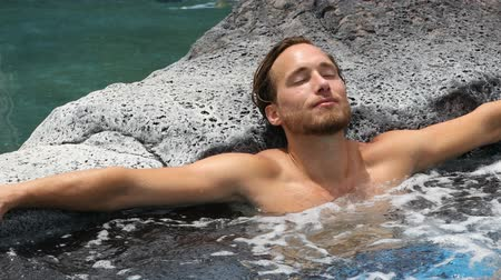 джакузи : Spa wellness - man relaxing in hot tub whirlpool jacuzzi outdoor at luxury resort spa retreat. Happy young male model relaxed resting in water on vacation travel holidays. Стоковые видеозаписи