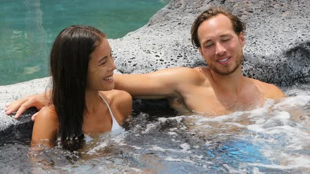 küvet : Romantic couple relaxing together in hot tub whirlpool jacuzzi luxury resort spa retreat Luxurious hotel travel vacation. People laughing talking having fun relaxed enjoying summer holidays.