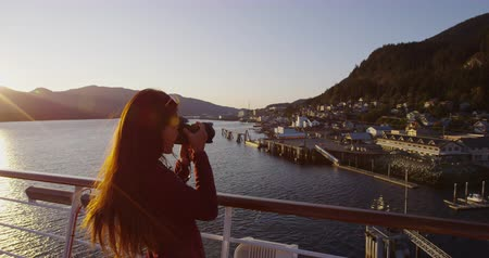 tomar : Alaska Cruise ship passenger photographing city of Ketchikan from cruise ship deck while sailing Inside Passage. Ketchikan is a famous Alaska cruise ship destination for tourist sightseeing.