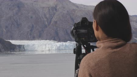 ledovec : Photographer tourist in Alaska. Cruise ship passenger photographing glacier, Glacier Bay National Park, Woman taking photo with SLR professional camera equipment on travel vacation. Margerie Glacier.