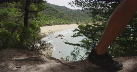 noga : New Zealand Hiking Tramping Travel Vacation in Abel Tasman National Park. Hikers hiking shoes and legs walking closeup with nature landscape view of Tonga Bay and Onetahuti beach from, New Zealand.