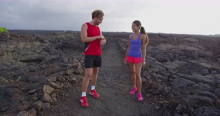 heart rate : Running athlete man and woman looking at heart rate monitor smartwatch. Runner talking looking at smart watch fitness tracker.