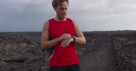 cronômetro : Running athlete man looking at heart rate monitor GPS watch smartwatch. Runner running to while looking at smart watch fitness tracker in action. Athlete runner training on trail run on Hawaii, USA.