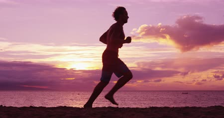 waga : Man running and jogging training at beach sunrise. Silhouette of male runner working out exercising alone on run. Fit fitness model running in SLOW MOTION.