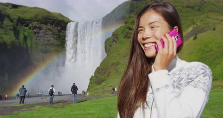 islandia : Woman tourist by waterfall Skogafoss on Iceland ttalking on phone with smart phone outdoor. Girl visiting in Icelandic nature landscape Wideo