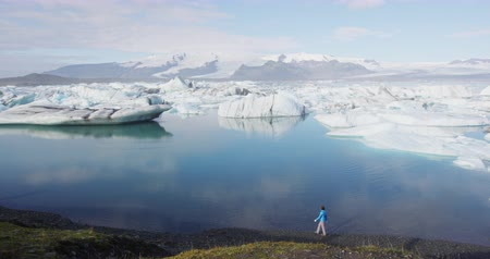 iceberg : Iceland tourist by Jokulsarlon glacier lagoon  glacier lake on Iceland. Woman walking outdoors by tourist destination landmark attraction in Vatnajokull National Park Stock Footage