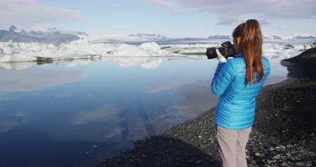 tomar : Photographer tourist on Iceland photographing nature landscape Jokulsarlon glacial lagoon  glacier lake on Iceland. Woman outdoors by tourist destination landmark attraction. Vatnajokull National Park