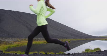 calzamaglia : Person running - woman runner on jogging on trail in full length on run outdoors in nature, Iceland. Fit female athlete training working out as part of healthy active lifestyle Filmati Stock