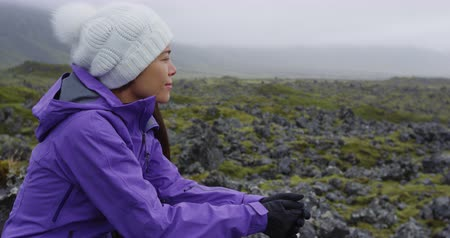 andar : Iceland. Asian woman hiker outdoors on hike resting. Tourist hiker enjoying view of Icelandic nature landscape wearing hat and jacket in summer on Snaefellsnes, West Iceland Vídeos