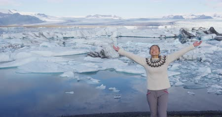 jokulsarlon : Happiness, serenity and success. Happy woman in nature with raised arms outstretched. Girl raising arms in serene pose, Jokulsarlon glacial lagoon, Vatna glacier, Vatnajokull National Park, Iceland Stock Footage