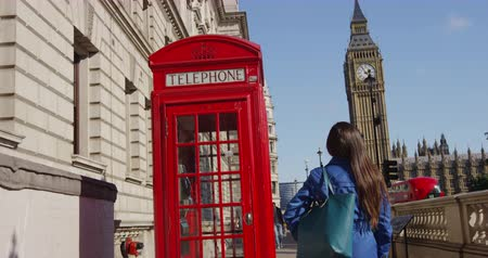 reino unido : Young female urban professional by red telephone booth and Big Ben in London, England, Great Britain. Casual business woman in trench coat walking in street enjoying leisure time in United Kingdom. Vídeos