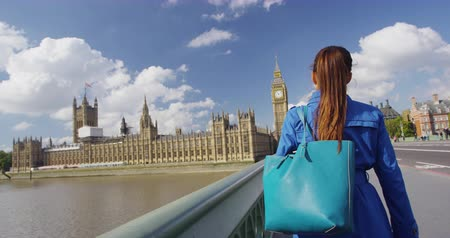 nakupování : Shopping woman with bag walking on Westminster Bridge in City of London. Young woman by Big Ben and Parliament Building walking, shopping and visiting famous destinations in London. SLOW MOTION.
