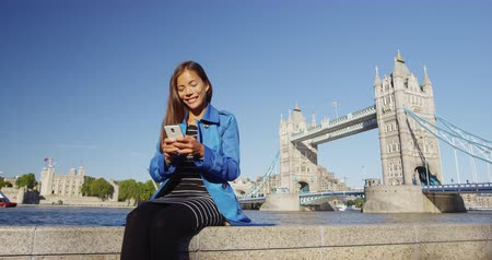 telephone tower : Phone - Young woman using smart phone app by London Tower Bridge. Smiling young professional businesswoman or tourist by River Thames by famous landmark, England, United Kingdom