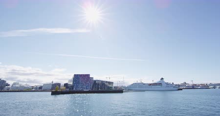 hostující : Cruise ship in Reykjavik harbour next to Harpa Concert Hall. Sunny summer day in Reykjavik