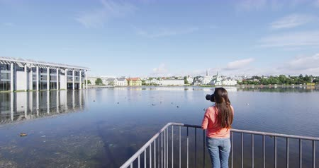 посещающий : Reykjavik Iceland tourist photographing in the city. Woman taking pictures of tourism landmarks and tourist attractions in Reykjavik. City Pond lake Tjornin and City Hall. SLOW MOTION.