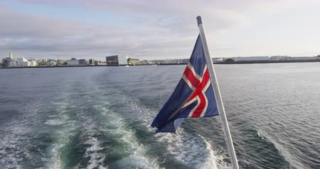 кит : Icelandic flag on Iceland on Reykjavik boat leaving harbour going on whale watching cruise. Iceland travel vacation tourism. RED EPIC SLOW MOTION., Стоковые видеозаписи