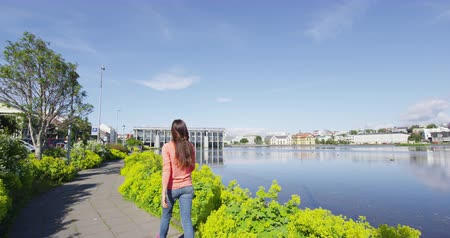 reykjavik : Reykjavik Iceland woman walking in city park on beautiful summer day with sun. City Pond Tjornin and City Hall. SLOW MOTION RED EPIC. Stock Footage