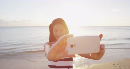 smíšené rasy osoba : Girl taking phone selfie video or photo using smartphone app on beach vacation travel. Multiracial Asian  Caucasian woman using mobile phone taking pictures at pretty sunset