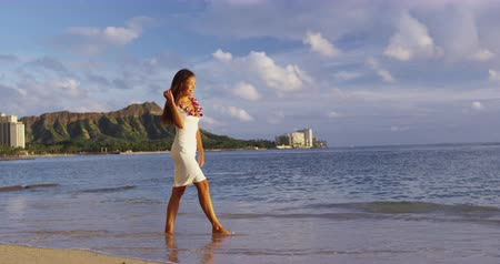 Оаху : Hawaii travel beach vacation - woman walking wearing hawaiian flower Lei. Pretty mixed race Asian Caucasian woman on beach resort., Waikiki, Oahu, Hawaii, USA Стоковые видеозаписи