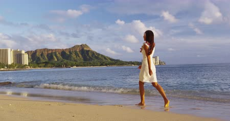 Оаху : Hawaii Waikiki travel beach vacation - woman walking wearing hawaiian flower Lei. Woman enjoying beach resort and view of famous Diamond Head., Waikiki, Oahu, Hawaii, USA. Стоковые видеозаписи