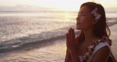 felvilágosodás : Spiritual - woman giving namaste gesture in yoga meditation on Hawaii wearing traditional Hawaiian flower lei. Meditating serene multicultural young Asian Caucasian woman at ocean beach sunset. Stock mozgókép
