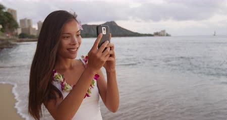 orkide : Happy young woman photographing using smartphone at Waikiki Beach. Smiling female tourist girl enjoying vacation at island in Honolulu wearing orchid lei garland taking photo. Stok Video