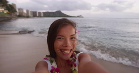 Оаху : Asian woman taking selfie at Waikiki Beach. Smiling beautiful female tourist is wearing orchid lei garland during vacation. Girl puckering lips blowing kiss at camera in Honolulu.