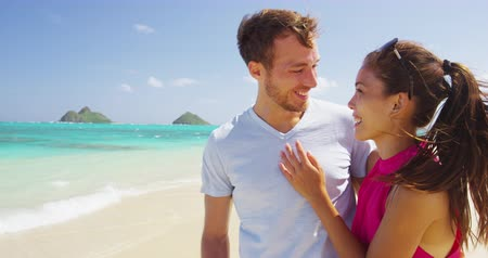 hawaje : Happy beach couple in love laughing having fun vacations. Joyful Asian and young Caucasian boyfriend and having fun on travel holiday on Lanikai beach, Oahu, Hawaii, USA