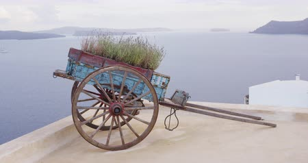 УВР : Europe Greece Santorini travel vacation nature landscape with decorative cart wagon on roof top in Oia, Santorini, Greek Islands, Greece, Europe.